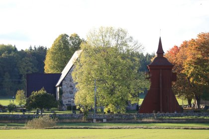 Medieval stone church with wooden bell tower in autumn sunlight