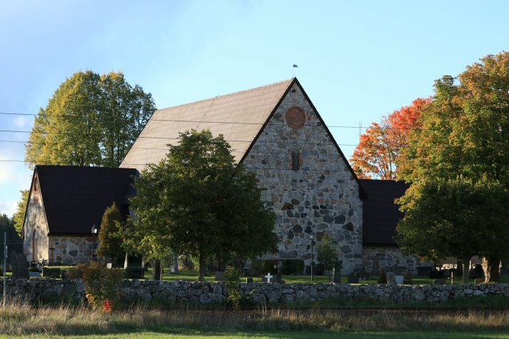 Gable of medieval stone church in autumn
